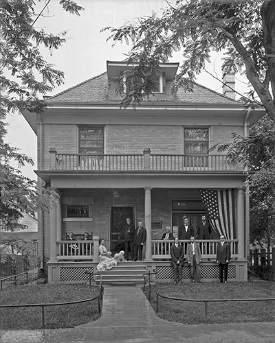 Celebrating the 4th of July in 1912, this gathering of family and friends reflects the popularity of the porch as a social gathering place. While not overly ornate, each detail of the porch from the roof balustrade to the turned columns to the simple lattice work facing the deck contributes to its character, creating in effect the dominant architectural feature of the building. Photo: © Utah State Historical Society